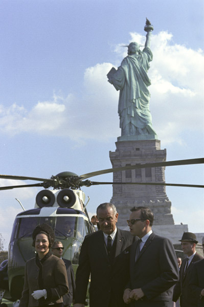 President Lyndon Johnson, Lady Bird Johnson and Bill Moyers behind the Statue of Liberty for the signing of the Immigration Act of 1965. ARC Identifier 2803427