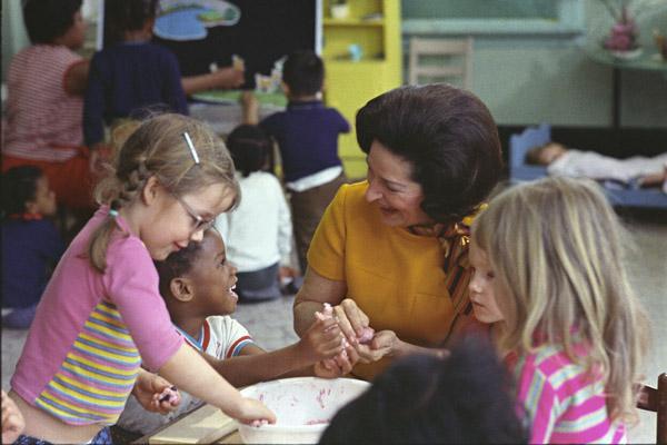 Lady Bird Johnson practices her active listening skills while visiting school children. (NARA Identifier 2803425)
